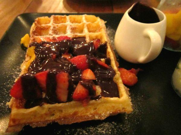 Waffle do Belga Corner coberto com a calda densa de chocolate belga e morangos picados